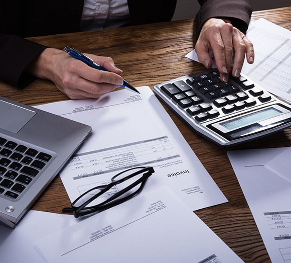 Person calculating invoices using electronic calculator