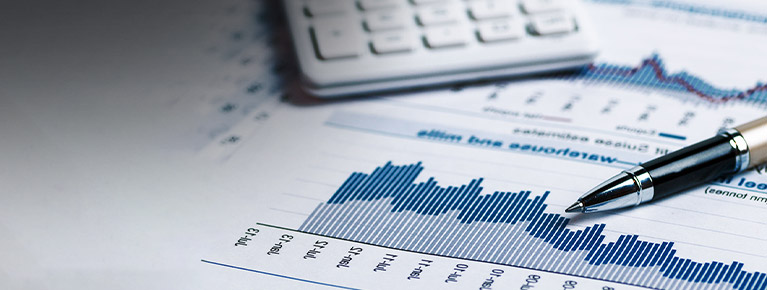 Pen and calculator on financial charts